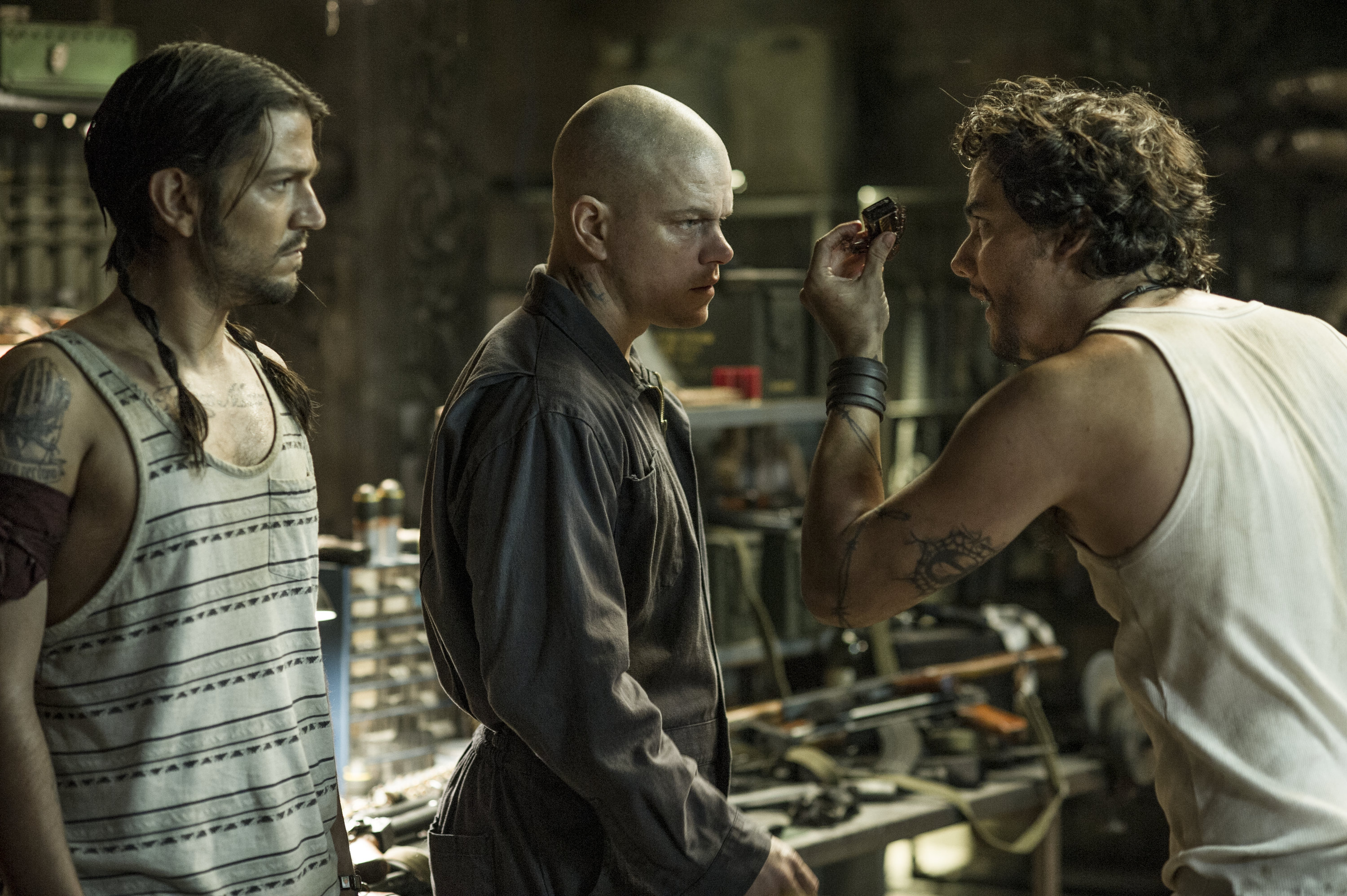 Max (MATT DAMON, center), Julio (DIEGO LUNA, left) and Spider (WAGNER MOURA) meet inside Spider's armory in Columbia Pictures' ELYSIUM.