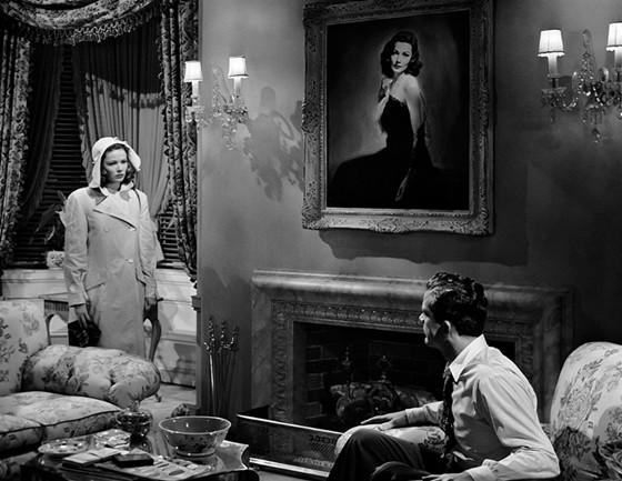 1944: Gene Tierney, as Laura, dressed in a raincoat and rainhat, stares solemnly at co-star Dana Andrews who plays Detective McPherson in the film 'Laura' directed by Otto Preminger.